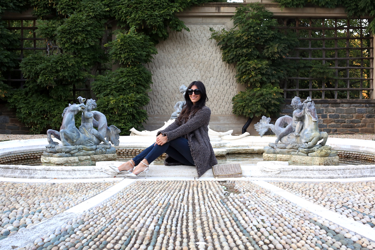 dumbarton-oaks-pebble-garden-fountain-iro-jacket-sitting-smiling